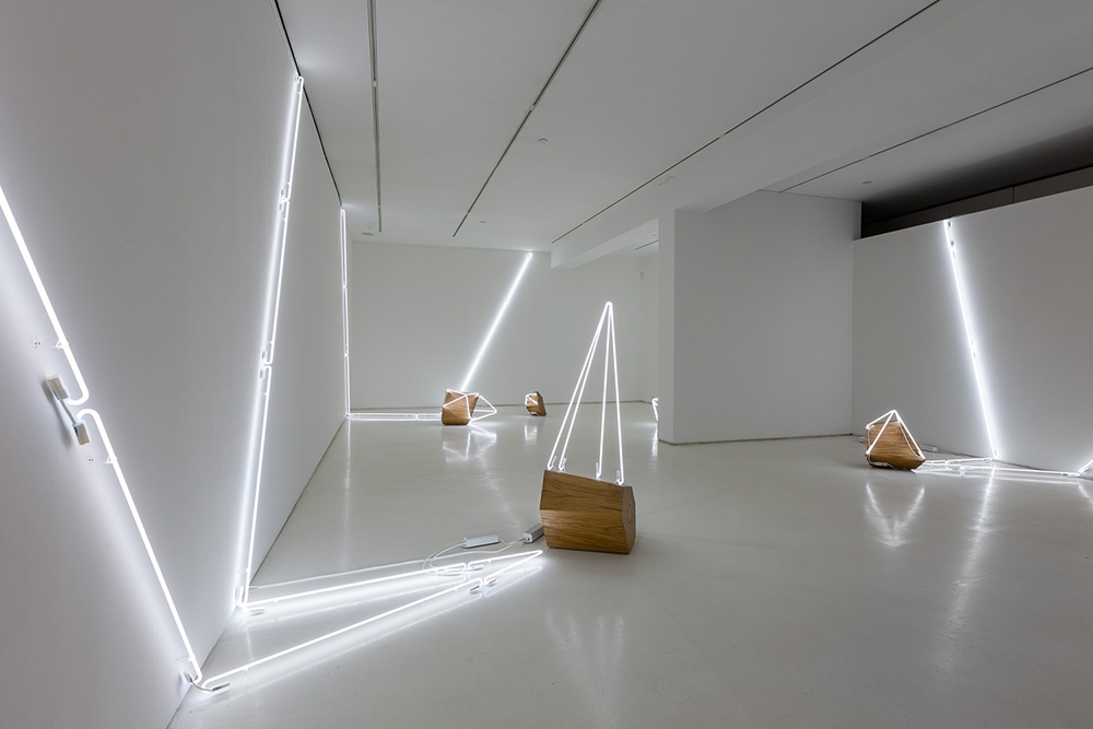Keith Lemley, Arboreal, 2015, chestnut, oak, and white neon, dimensions variable. At Mixed Greens. Courtesy of the artist.